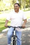 Vélo hispanique aîné d'équitation d'homme en stationnement Images stock