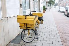 Vélo jaune allemand traditionnel pour la distribution du courrier photographie stock