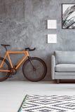 Vélo orange à côté de sofa photos stock