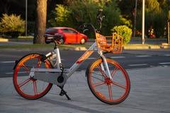 Vélo orange moderne pour le loyer sur la rue de Madrid image stock