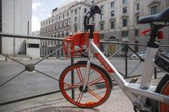 Vélo orange moderne pour le loyer sur la rue de Madrid, Espagne photographie stock libre de droits