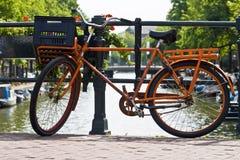 Vélo orange sur un canal d'Amsterdam Images libres de droits