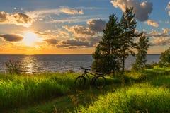 Vélo par la rivière dans le coucher de soleil La Sibérie, Russie Photographie stock