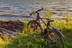 Vélo par la rivière dans le coucher de soleil La Sibérie, Russie Photos stock