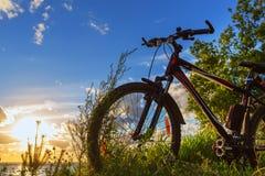Vélo par la rivière dans le coucher de soleil La Sibérie, Russie Photographie stock libre de droits