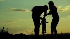 Vélo réparant sur le coucher du soleil banque de vidéos