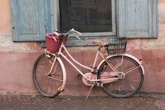 Vélo rose nostalgique contre la façade de maison images stock