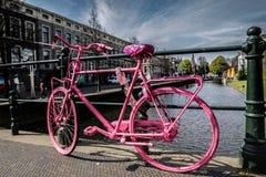 Vélo rose sur le pont en canal Photographie stock libre de droits