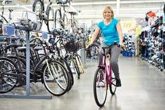Vélo sportif attrayant d'essai de femme dans le magasin Photo libre de droits