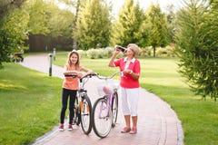 Vélo supérieur actif d'équitation de femme en parc Photo libre de droits