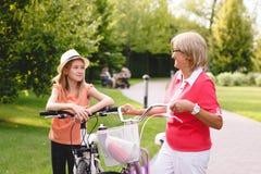 Vélo supérieur actif d'équitation de femme en parc Photos libres de droits