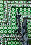 Vélo sur le plancher de tuiles vert Photos libres de droits