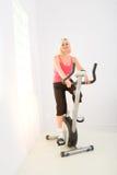 vélo tournant à l'extérieur le fonctionnement de femme image stock