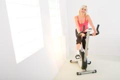 vélo tournant à l'extérieur le fonctionnement de femme photographie stock