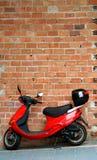 Vélomoteur ou motocyclette rouge se reposant ou se penchant contre un mur de briques. images libres de droits
