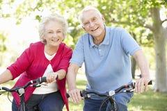 Vélos aînés d'équitation de couples Photo stock