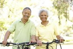 Vélos aînés d'équitation de couples en stationnement Images libres de droits