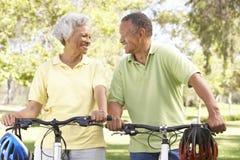 Vélos aînés d'équitation de couples en stationnement Photos libres de droits