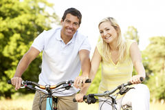 Vélos d'équitation de couples dans la campagne Photographie stock libre de droits