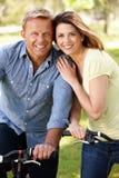 Vélos d'équitation de couples en stationnement Photos stock
