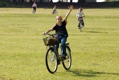 Vélos d'équitation de famille sur le pré Photographie stock libre de droits