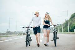 Vélos de marche de jeunes couples ensemble sur la route Photos stock
