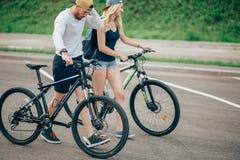 Vélos de marche de jeunes couples ensemble sur la route Photos libres de droits