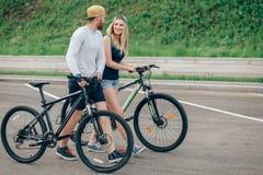 Vélos de marche de jeunes couples ensemble sur la route Images stock