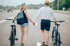 Vélos de marche de jeunes couples ensemble sur la route Image stock