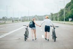 Vélos de marche de jeunes couples ensemble sur la route Photo stock