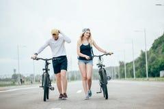 Vélos de marche de jeunes couples ensemble sur la route Photographie stock