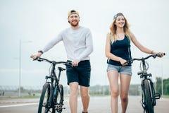 Vélos de marche de jeunes couples ensemble sur la route Images libres de droits