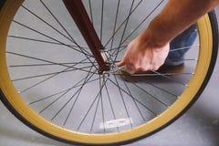 Vélos de réparation de thème Le plan rapproché d'une utilisation caucasienne de main du ` s d'homme un vélo d'outil de bricolage  Image libre de droits