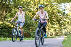 Vélos de tour des jeunes autour du parc Le concept du recyclage photographie stock