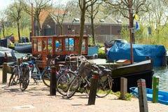 Vélos et bateaux de pêche traditionnels de Botter de Néerlandais dans le petit port du village de pêche historique aux Pays-Bas Photos stock