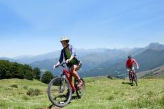 Vélos folâtres d'équitation de couples dans les montagnes images libres de droits