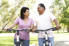 Vélos hispaniques aînés d'équitation de couples en stationnement Images stock