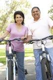 Vélos hispaniques aînés d'équitation de couples en stationnement Photo libre de droits