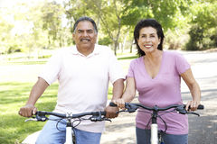 Vélos hispaniques aînés d'équitation de couples en stationnement Images libres de droits