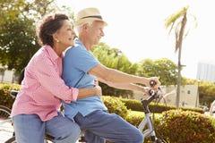 Vélos hispaniques aînés d'équitation de couples en stationnement Photographie stock libre de droits