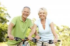 Vélos mûrs d'équitation de couples Photographie stock libre de droits