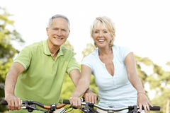 Vélos mûrs d'équitation de couples Photographie stock