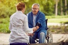 Vérifiant l'évaluation d'hypertension de la tension artérielle m plus âgé photos libres de droits
