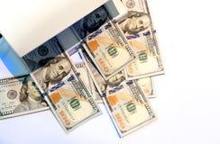 Vérification de cent billets de banque du dollar avec la lumière UV ou Images libres de droits