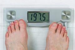 Vérification du poids corporel sur l'échelle Photos stock