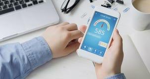 Vérification du score de crédit sur le smartphone utilisant l'application Le résultat est MOYEN banque de vidéos