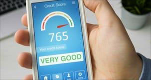 Vérification du score de crédit sur le smartphone utilisant l'application Le résultat est TRÈS BON banque de vidéos