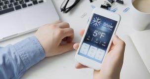 Vérification du wather utilisant le smartphone APP Milou et froid banque de vidéos