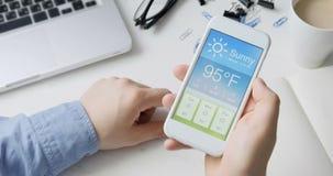 Vérification du wather utilisant le smartphone APP Temps chaud et ensoleillé banque de vidéos