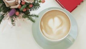 Vérifiez la caméra avec la tache floue par le cappuccino dans une tasse avec un coeur sur le crema clips vidéos